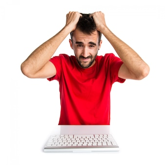 彼のキーボードで作業している挫折したコンピュータ技術者