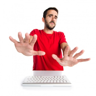 Компьютерный техник работает со своей клавиатурой, делая знак остановки