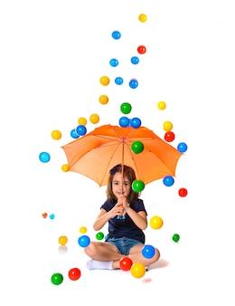 色のボールを雨の中に傘を持っている少女