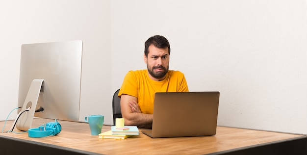 オフィスでラップトッと働く男はちょっと神経質で、歯を押すのを怖がっている