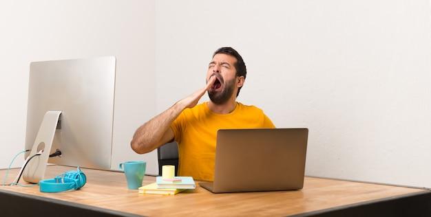 待っているオフィスでラップトッと働いていて、広い口を手で覆う男