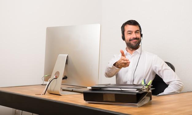 良い取引の後にオフィスのハンドシェイクでテレマーケティングの男