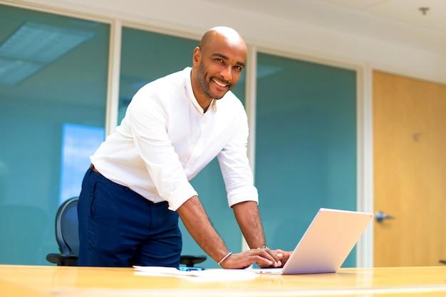 彼のラップトップを持つオフィスで若いアフロアメリカンビジネスマン