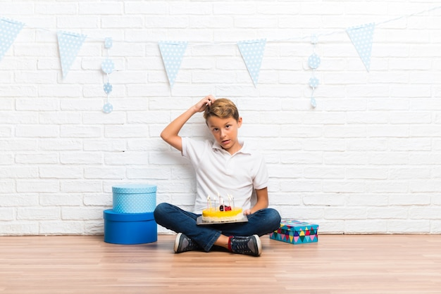 ケーキの立っていると考えを考えて彼の誕生日を祝う少年