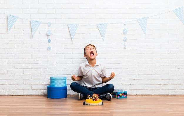 ケーキで彼の誕生日を祝っている少年は猛烈なジェスチャーで腹を立てて腹が立つ