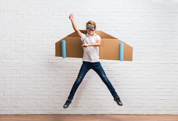 段ボールの飛行機の翼で跳んでいる少年