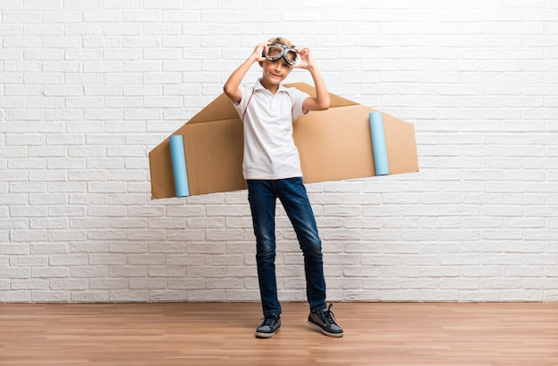 段ボールの飛行機の翼をしている少年