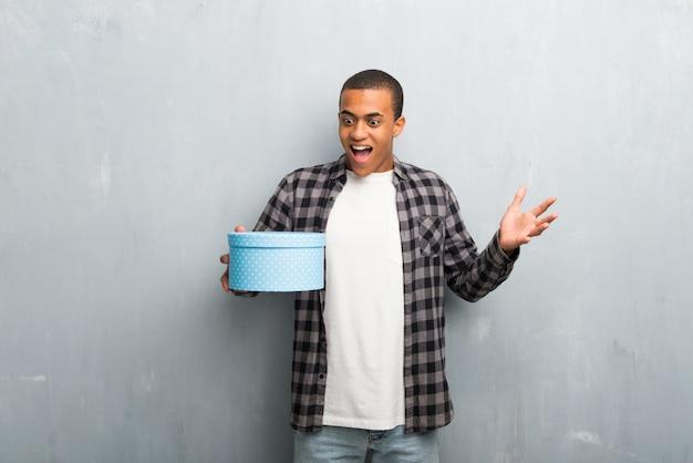 市松模様のシャツを持つ若いアフリカ系アメリカ人男性は贈り物を与えられているため驚いた