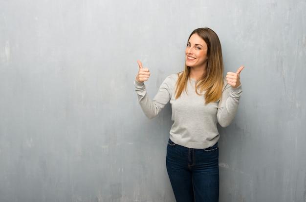 両手で親指ジェスチャーを与えると笑みを浮かべて織り目加工の壁に若い女性