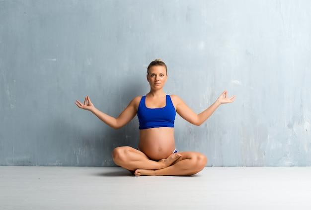 ヨガをやっている金髪の妊娠中の女性