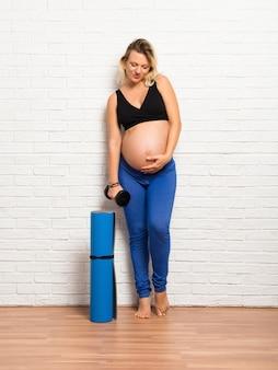 屋内でマット運動をしているスポーツ金髪妊娠中の女性