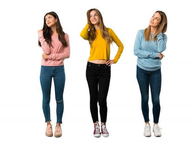 見ながらアイデアを考えているカラフルな服を持つ人々のグループの全身ショット