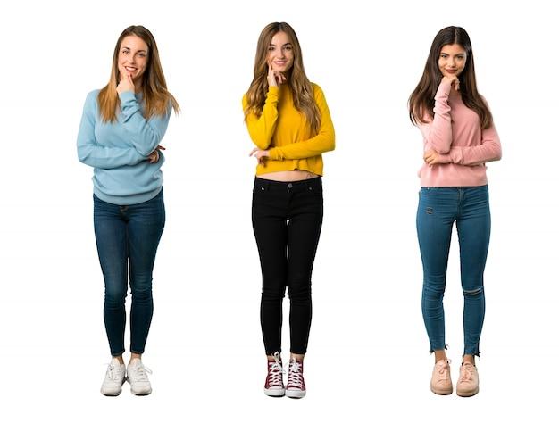 カラフルな服を笑顔で正面を見ている人々のグループの全身ショット