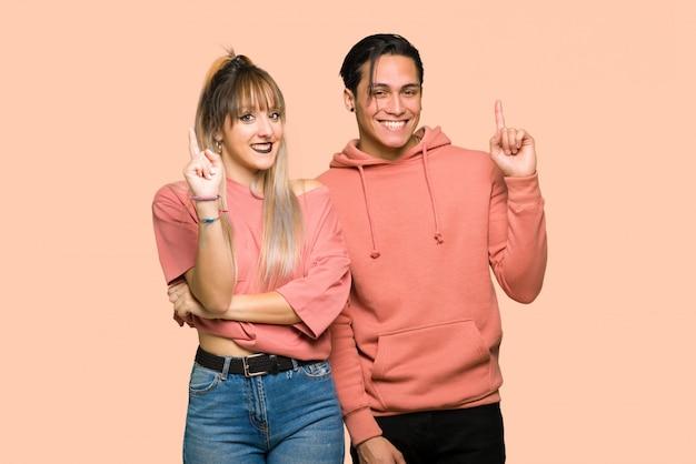 バレンタインの日に若いカップルを示すとピンクの背景の上の最高の印で指を持ち上げる