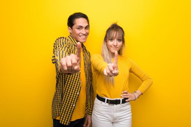 バレンタインの日に示していると指を持ち上げる鮮やかな黄色の背景の上の若いカップル