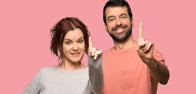 バレンタインの日を示すと孤立したピンクの背景の上に指を持ち上げるのカップル