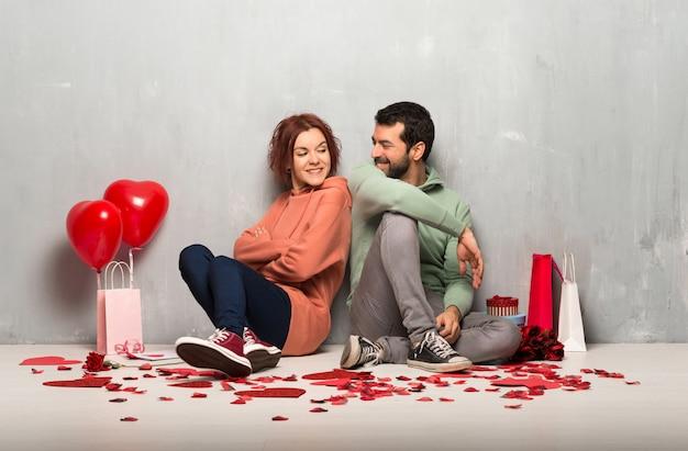 Пара в день святого валентина, держа руки скрещенными, глядя друг на друга