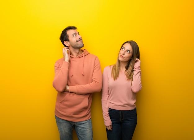 В день святого валентина группа из двух человек на желтом фоне, думая идею, почесывая голову