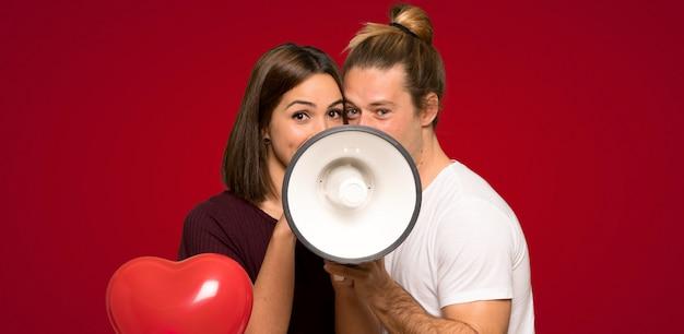 Пара в день святого валентина кричит через мегафон на красном фоне