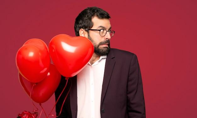 バレンタインの日に男は少し緊張し、赤い背景の上に歯を押すと怖い