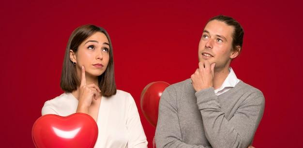 赤い背景を見上げながらアイデアを考えてバレンタインデーのカップル