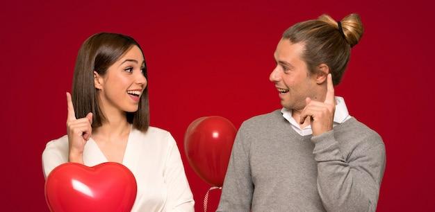 赤い背景の上に指を指すアイデアを考えてバレンタインデーのカップル