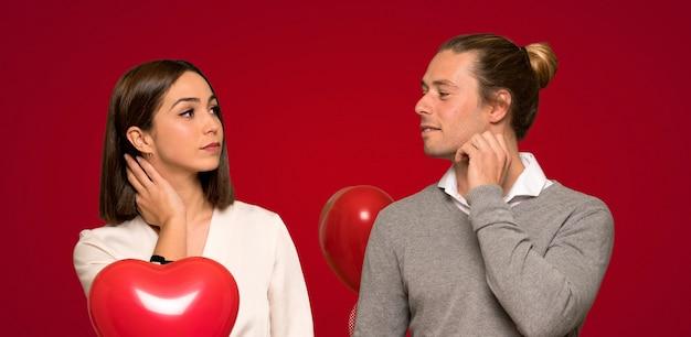 赤い背景の上に頭を掻きながらアイデアを考えてバレンタインデーのカップル