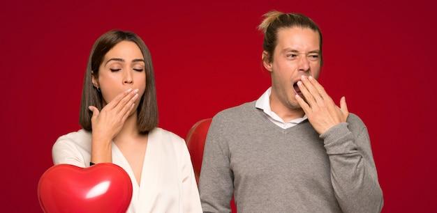 あくびをし、手で広い口を覆っているバレンタインの日のカップル