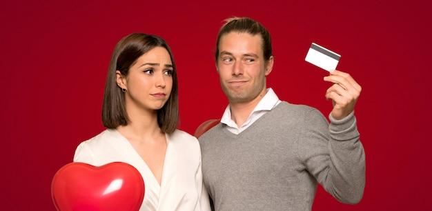 バレンタインの日に赤い背景の上に携帯電話で音楽を聴くのカップル