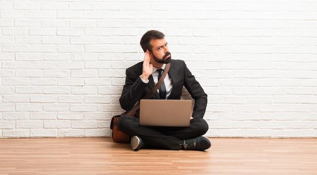 耳に手を置くことによって何かを聞いて床に座って彼のラップトップを持ったビジネスマン