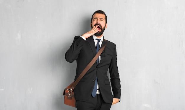 あくびと手で大きく開いた口を覆っているひげを持ったビジネスマン