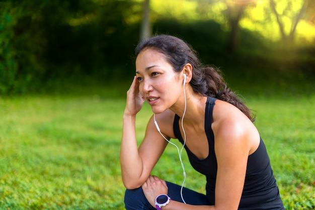 スポーツアジアの女性のヘッドフォンで音楽を聴くとトレーニングの後の残り