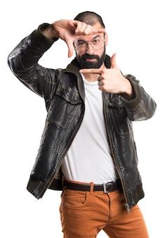 彼の指に焦点を当てた革ジャケットを持つ男