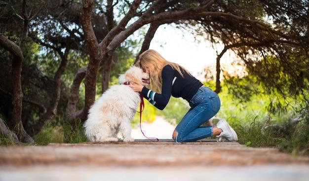 公園で彼女の犬を持つ若い女の子