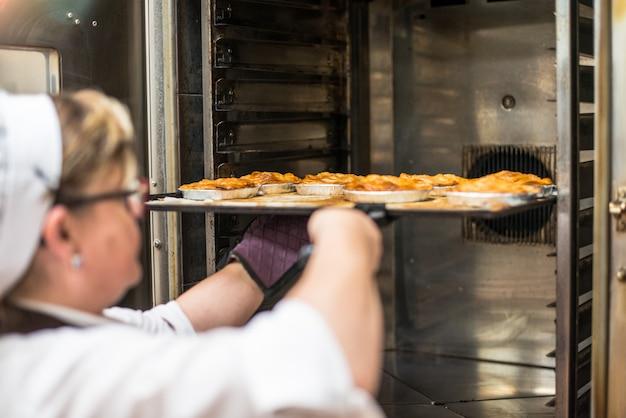 オーブンでケーキを調理するパン屋さんの台所で女性