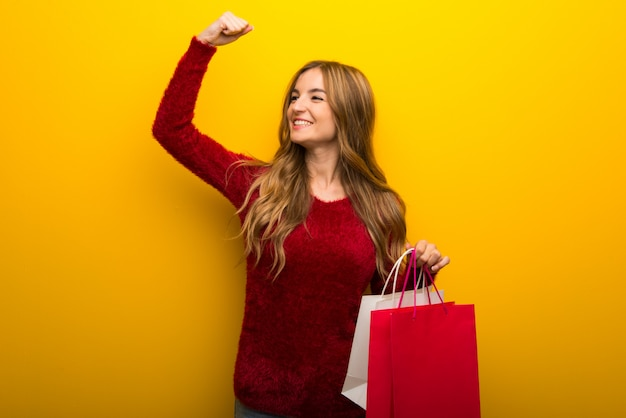 Молодая девушка на ярком желтом фоне держит много сумок в победной позиции