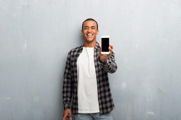 カメラを見て、携帯電話を使用しながら笑顔の市松模様のシャツと若いアフリカ系アメリカ人男性