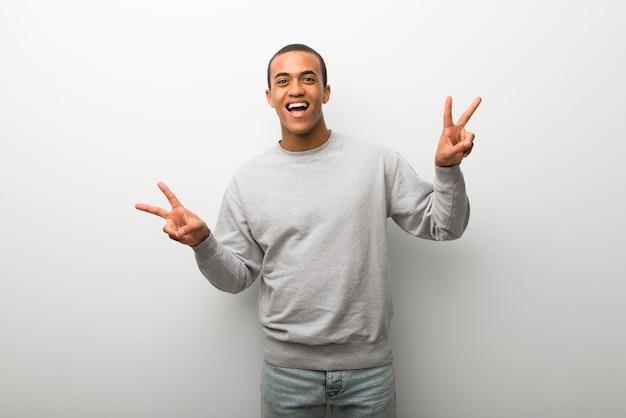 白い壁の背景にアフリカ系アメリカ人の男笑顔と両手で勝利のサインを示す