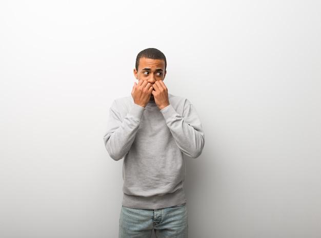 Афро-американский мужчина на белом фоне стены немного нервничает и боится положить руки в рот