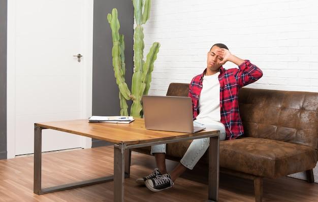 疲れて病気の表現とリビングルームでのラップトップを持つアフリカ系アメリカ人の男