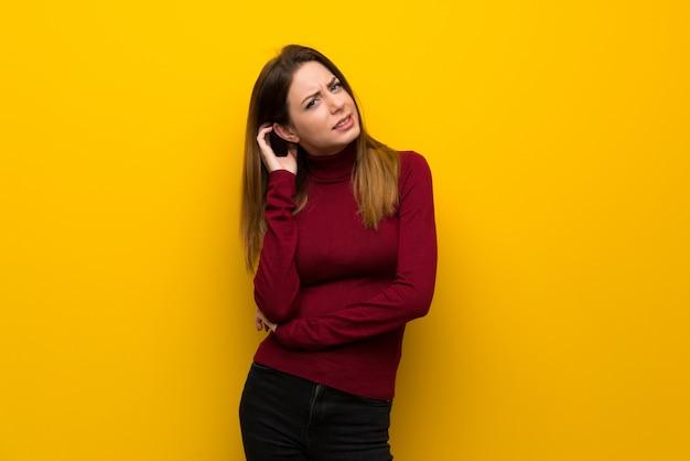 疑問を持つ黄色の壁の上のタートルネックを持つ女性