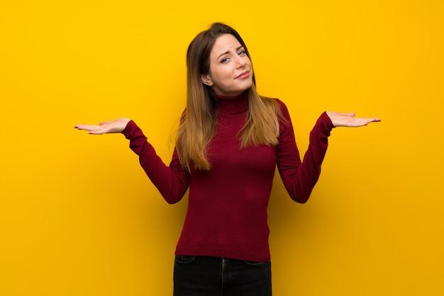 手を上げながら疑問を持つ黄色の壁の上のタートルネックを持つ女性