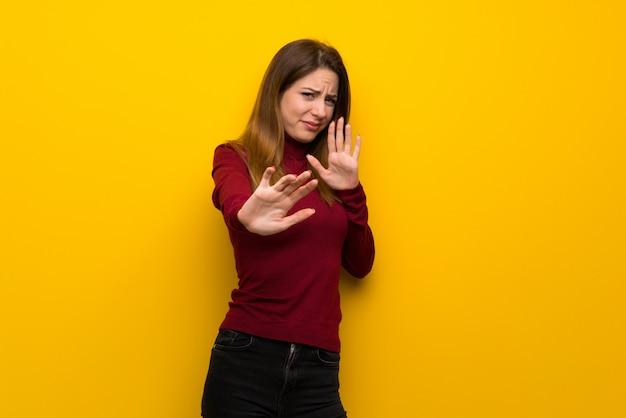 Женщина с водолазкой над желтой стеной нервно и испуганно протягивает руки вперед