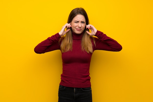 欲求不満と耳を覆う黄色の壁の上のタートルネックを持つ女性