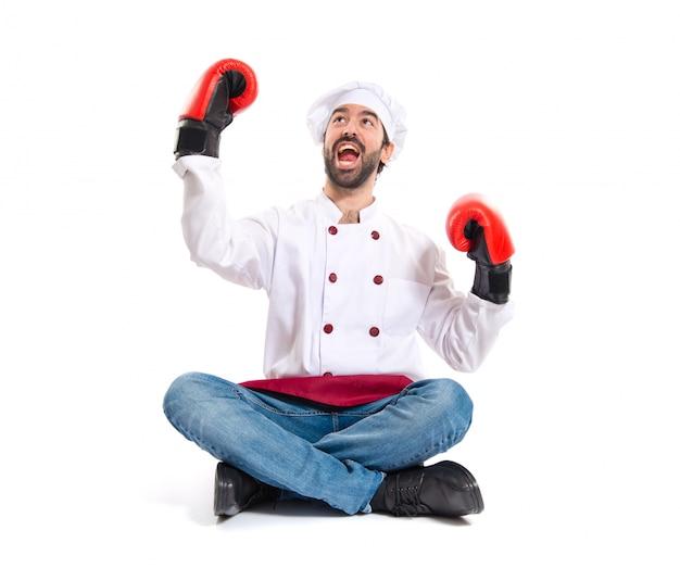 Шеф-повар с боксерскими перчатками, сидящими на полу