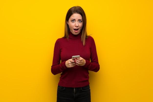 黄色の壁の上のタートルネックを持つ女性は驚いてメッセージを送信する