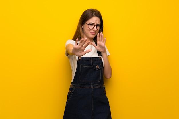 Женщина над желтой стеной нервно и страшно протягивает руки вперед