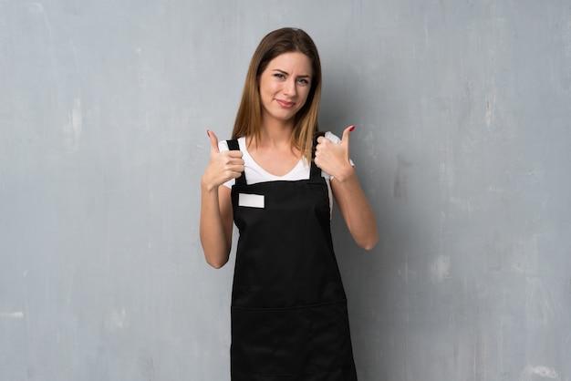 親指を立てるジェスチャーと笑顔の従業員女性