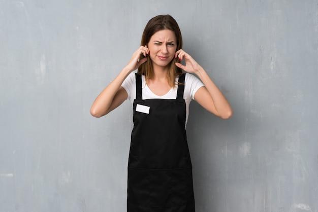 イライラして手で耳を覆っている従業員女性
