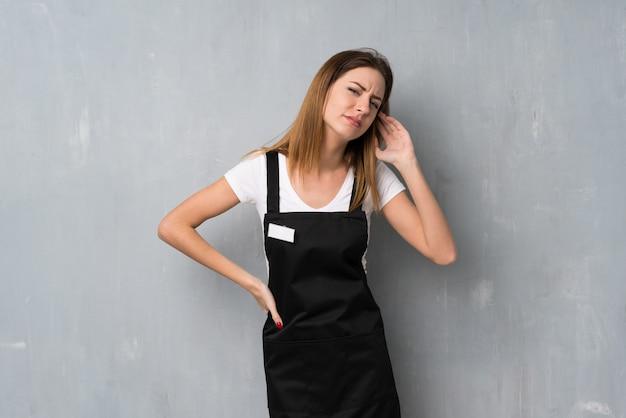 耳に手を置くことによって何かを聞いている従業員女性